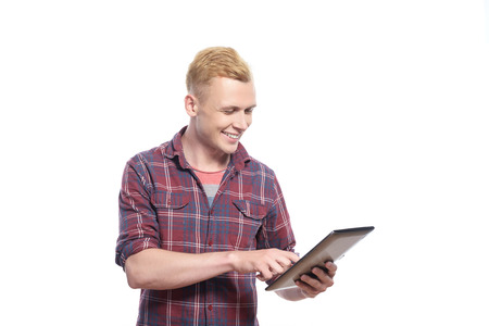youthful: Work with smile. Smiling youthful man looking at tablet and typing on white isolated background.