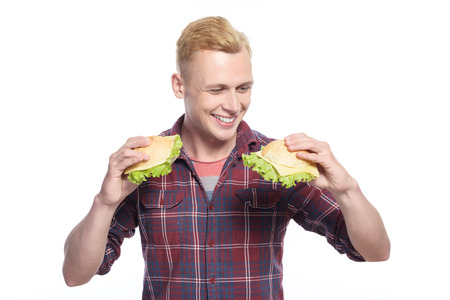 youthful: Which to choose. Handsome youthful man holding two sandwiches looking at them and choosing on isolated white background.