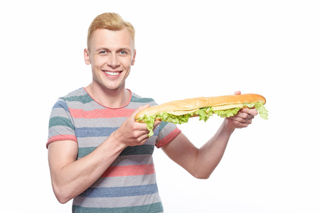 sensational: So long. Smiling young man showing off his sandwich made of long loaf on isolated white background. Stock Photo