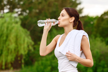 satisfying: Satisfying thirst. Young pleasant woman having rest after sport exercises holding bottle of water and white towel. in park Stock Photo