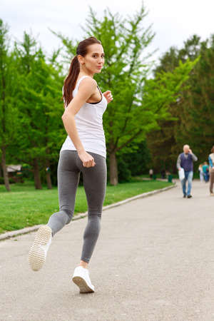 youthful: Process is important. Youthful woman is practicing running in green park Stock Photo