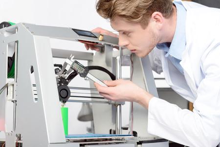 impresora: Hermoso joven científico que mide algo con pinzas en 3D-impresora, vistiendo bata blanca de laboratorio en laboratorio Foto de archivo