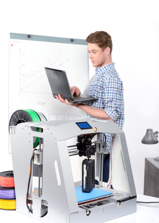 lab tech: Selective focus on a 3d-printer on a table, young handsome student standing and holding a laptop working on it , flip chart board with diagram on a background