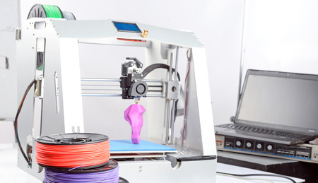 Pasture of a 3d-printer during printing a violet item, laptop standing on a table and colorful hanks of plastic, selective focus