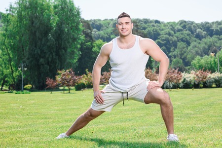 spread legs: Portrait of a young handsome sportsman standing with his legs spread wide and leaning on the left leg holding his left hand on it and right hand on his right leg, wearing white sportswear