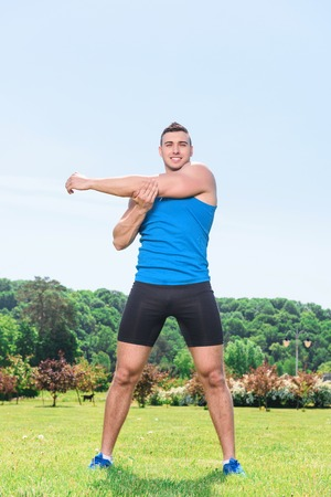 spread legs: Portrait of a young handsome muscular sportsman standing with his legs wide spread and holding his left arm with right hand, wearing black blue sportswear during training in the park full length