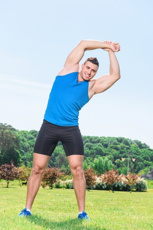 spread legs: Portrait of a young handsome muscular sportsman standing titled with his legs wide spread and holding his hands above his head, wearing black blue sportswear during training in the park full length