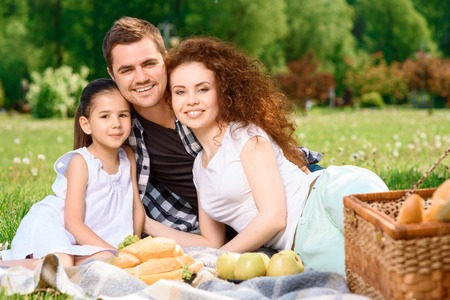 Portrait of a young happy family enjoying the picnic in a park sitting on a plaid on a green grass smiling cheerfully, wicker basket for picnic and sandwiches near photo