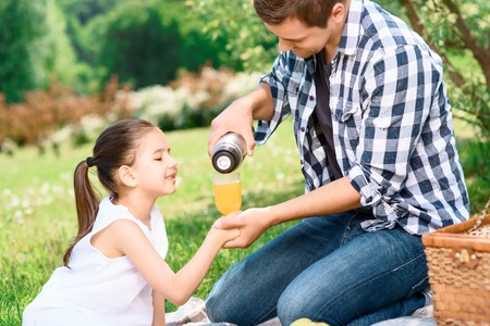 Portrait of a young happy father pouring a fruit juice to a glass holding by his daughter smiling sitting on a plaid on a green grass, enjoying the picnic photo