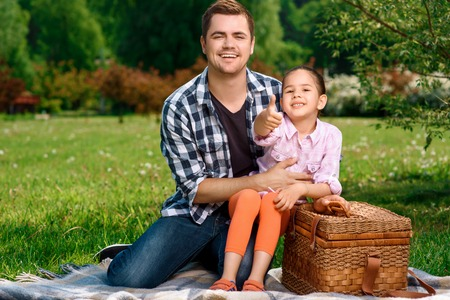 hugging knees: Happy handsome father sitting on a plaid on a green grass holding his small pretty daughter on his knees and hugging her, both smiling, wicker basket for picnic near