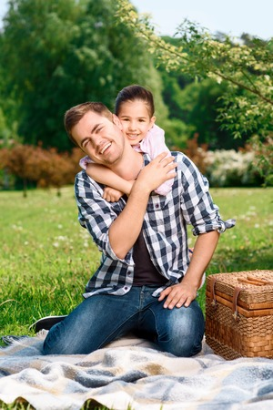 Happy handsome father sitting on a plaid on a green grass laughing while his pretty small daughter hugging him from the back smiling, on a picnic in a park photo