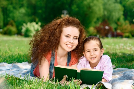 Beautiful young happy mother reading a green book with her small charming daughter lying on a plaid on a picnic in the park photo