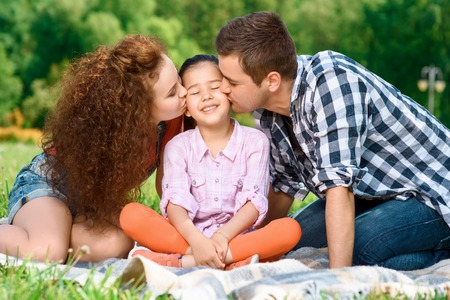 Lovely family. Little happy girl sitting on a plaid on a green grass and smiling cheerfully when her mother and father kissing her from two sides, enjoying family picnic in a park photo