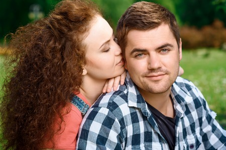 Sweet couple. Beautiful young woman cuddling with her smiling man sitting on a grass in the park enjoying a picnic, close up photo