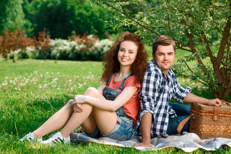 Lovely couple enjoying summer sitting on a plaid on a green grass in a park smiling happily, wicker basket for picnic near photo