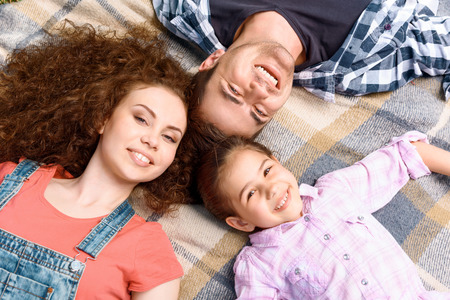 Top view portrait of a young happy family of father mother and pretty daughter lying smiling on a checkered plaid on a picnic , top view photo