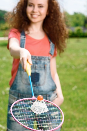 Portrait of a young beautiful lady standing in a park stretching a racquet in front of her with a shuttlecock on it, selective focus photo