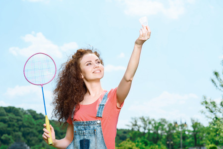 Portrait of a young beautiful lady standing in a park holding a racquet above her and a shuttlecock in another hand, ready for making a serve photo