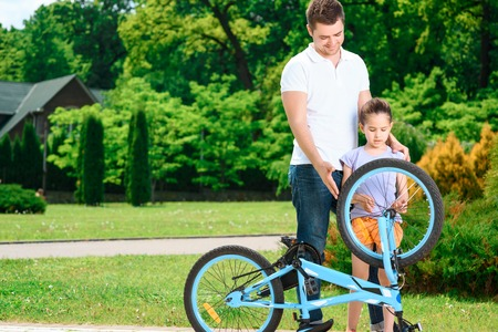 Portrait of a smiling father standing next to his small pretty daughter in a green park and a blue bicycle upside down, both exploring the wheel photo