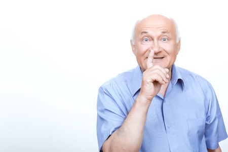 laugher: Keep silence. Cheerful grandfather holding the finger in front of the face while standing isolated on white background. Stock Photo