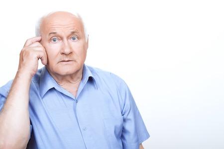 vejez feliz: Perplejidad de la mente. Abuelo Desconcertado sosteniendo el dedo índice en la sien mientras pensaba Foto de archivo