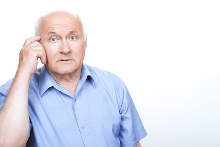 vecchiaia: Perplessità di mente. Perplesso nonno tiene il dito indice sulla tempia mentre il pensiero Archivio Fotografico