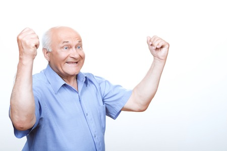 relaxed man: We are the champions. Joyful grandfather keeping his hands up while rejoicing in victory Stock Photo