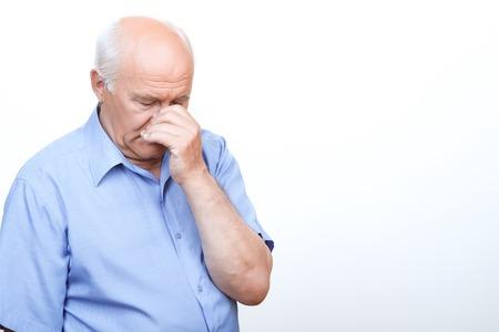 laugher: Feeling hopeless. Distempered grandfather touching his nose and keeping eyes closed while standing  isolated on white background. Stock Photo