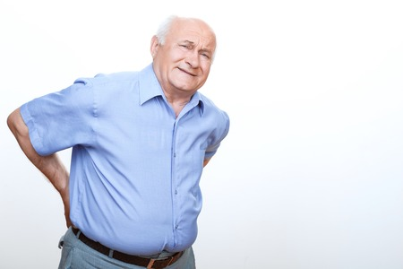 senior pain: Feeling pain. Exhausted grandfather leaning frontways and touching his back with hands Stock Photo