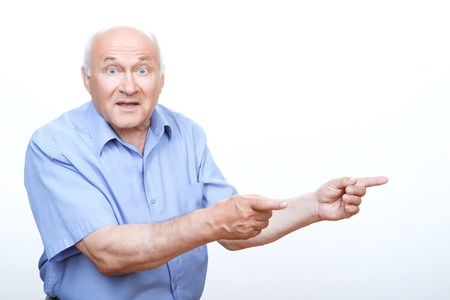 Look here. Astonished grandfather looking surprised and pointing to the left with two hands.