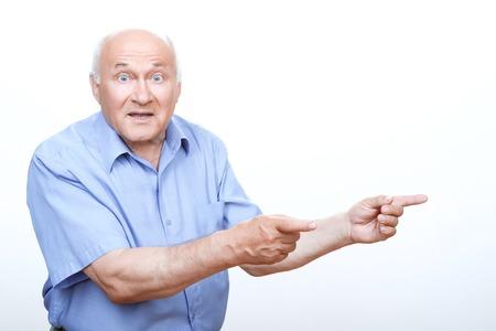 vejez feliz: Mira aqu�. Abuelo asombroso que mira sorprendido y apuntando hacia la izquierda con las dos manos.