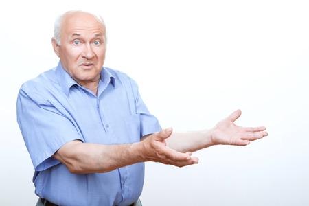 vejez feliz: Sentirse confundido. Abuelo Desconcertado sosteniendo su mano en frente de �l con las patas para arriba mientras que de pie aislado en fondo blanco. Foto de archivo