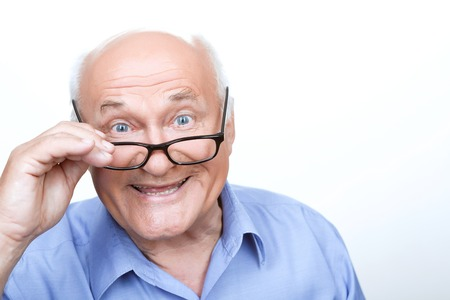 Like reading. Pleasant grandfather wearing glasses and holding them while smiling on white background. Stock Photo