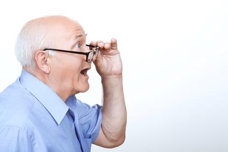 vejez feliz: Que sorpresa. Abuelo sorprendida que sostiene la mano de los anteojos y mostrando asombro mientras está de pie media cara
