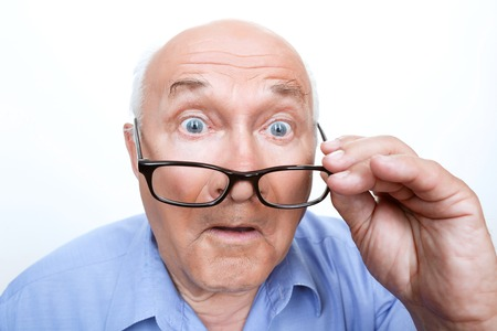 Great wonder. Close up of astonished grandfather holding glasses and looking straight. Stock Photo