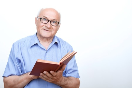 favorite book: Favorite book. Agreeable grandfather holding the book and looking straight while standing isolated on white backround. Stock Photo