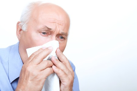 man close up: Severe cold. Sick grandfather holding handkerchief and sneezing while having cold