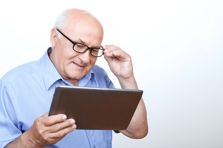 agreeable: Overwhelming network. Agreeable grandfather touching glasses and holding laptop with his glance down while surfing through the Internet