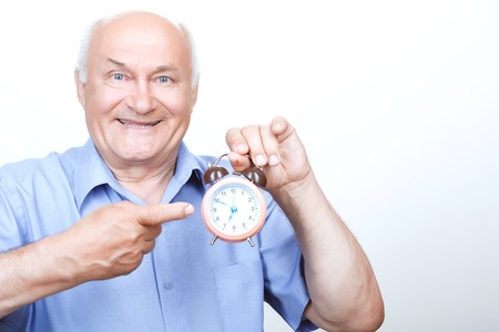 vivacious: Wake up. Vivacious grandfather pointing the alarm clock and smiling while holding it in hands