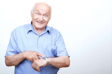 looking ahead: It is high time. Smiling grandfather pointing his wristwatch and looking ahead while standing isolated on white background.
