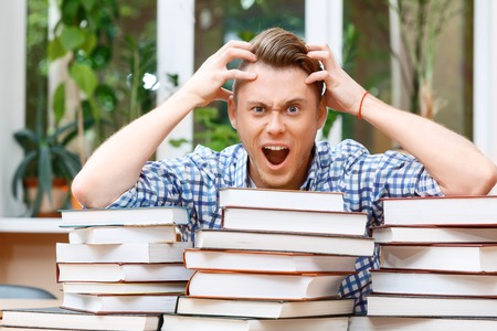 forgot: Forgot something important. Portrait of a handsome smart student sitting behind a big stack of books in a library, holding his head opening his mouth and looking very shocked