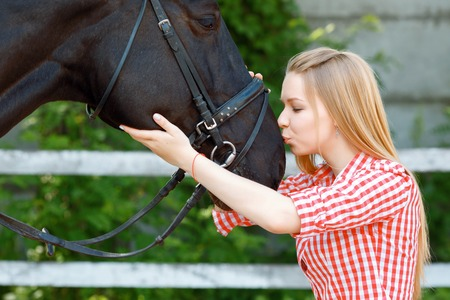 horse love horse kiss animal love: Reveling in kissing. Young girl touching and kissing the horse while standing nearby and expressing positivity. Stock Photo