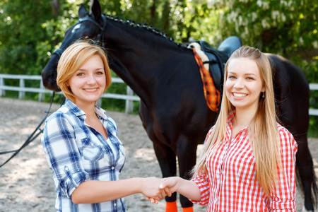 amicable: Amicable relationships. Smiling girls having optimistic mood and shaking hands with dark horse standing in the background. Stock Photo