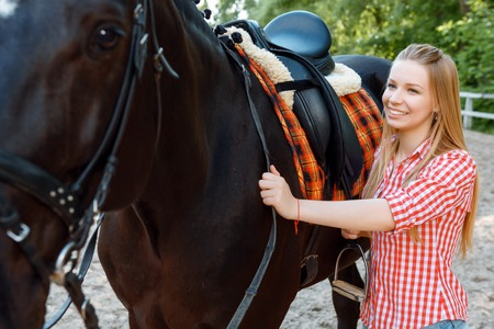 green life: Feeling glad. Smiling young girl touching riding bridle and keeping her glance on the horse. Stock Photo