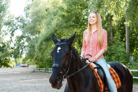 brisk: Brisk mood. Smiling girl sitting in the saddle and looking ahead while enjoying riding.