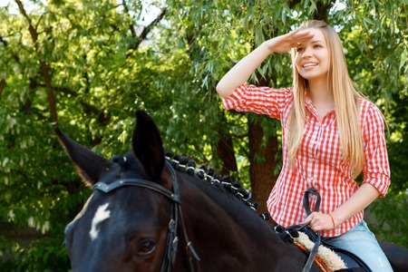 low  angle: Taking pleasure. Low angle photo of vivacious girl sitting in the saddle and holding hand near her forehead. Stock Photo