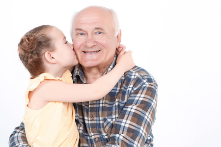 abuelo: Retrato de un abuelo sentado sonriendo y sosteniendo su pequeña nieta sobre sus rodillas, besando su mejilla, aislado en un fondo blanco Foto de archivo