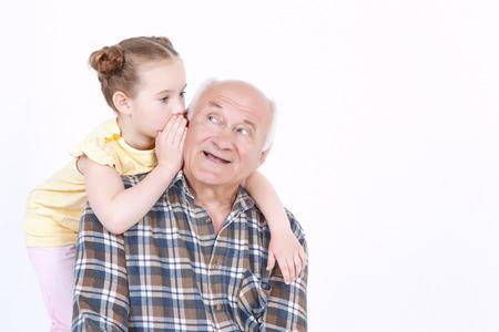 Porträt einer Großvater sitzen lächelnd, während seine hübsche kleine Enkelin umarmt ihn von hinten und flüsterte ihm ein Geheimnis zu Ohr, isoliert auf einem weißen Hintergrund