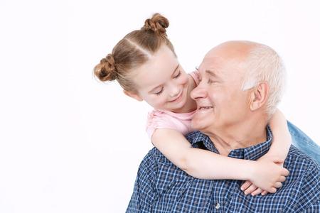 abuelo: Retrato de un abuelo de uniforme azul y camisa a cuadros de estar y pequeña nieta bonita de pie detrás de él sonriendo y abrazos, mirando el uno al otro, aislado en un fondo blanco Foto de archivo