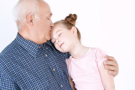 eyes closing: Portrait of a grandfather wearing blue checkered shirt hugging his small pretty granddaughter and kissing her forehead while she is closing eyes , isolated on a white background